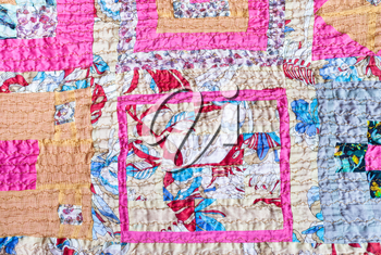 textile background - ornamental patchwork scarf stitched from various silk strips and crushed pink cotton fabric