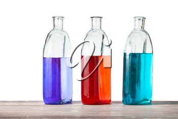 glass bottles with color ink solutions on wooden board with cutout background