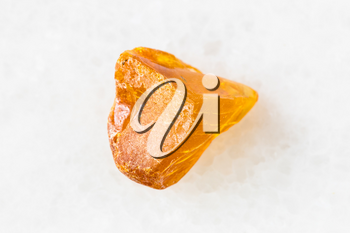 closeup of sample of natural mineral from geological collection - piece of Amber gemstone on white marble background from Baltic Sea, Kaliningrad, Russia
