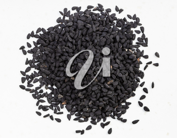 top view of pile of Nigella sativa seeds (black caraway) close up on gray ceramic plate