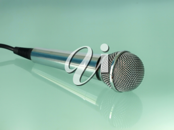 Silver metallic microphone on a transparent blue background.