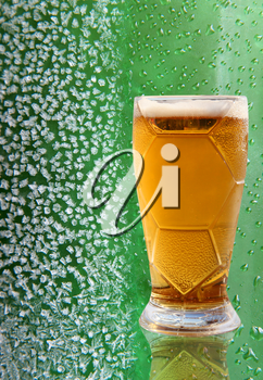 Fresh beer glass with reflection on ice crystals and drips green background.