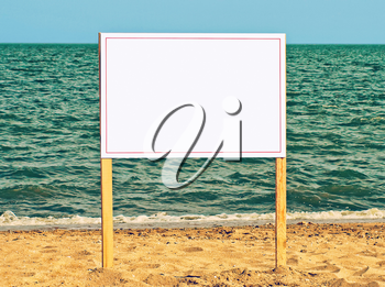 Blank billboard on sandy beach against of sea surf.Just add your text.