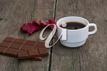 white cup of coffee, chocolate and red leaf, on a wooden table, a still life a subject drinks