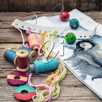 Yarn and thread for embroidering on cloth by hand on a wooden surface.Tinted