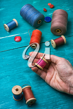 human hand and thread with buttons on turquoise wooden background