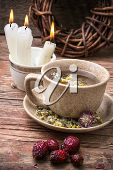 fragrant chamomile tea and burning candles in rustic style.Selective focus