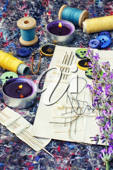 buttons and thread on background of cut branches of lavender.