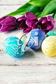 Decorated with painted Easter eggs and bouquet of tulips on light background