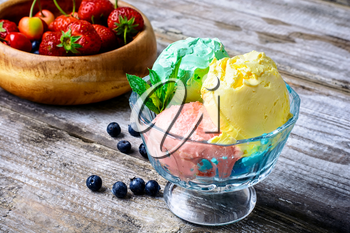 Bowl with fruit ice cream scattered on background of blueberries