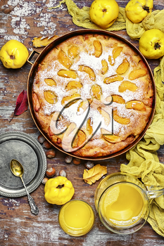 Autumn pie with ripe fruits of quince in a rustic style