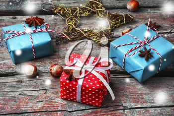 Three boxes with Christmas gifts on retro wooden background