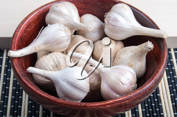 Spices for cooking - garlic in a wooden brown bowl closeup