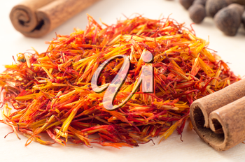 Condiments and spices - cinnamon sticks and fragrant saffron close-up with shallow depth of focus.