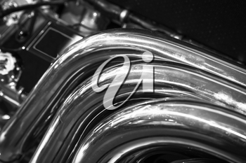 Chromed exhaust pipes. Shiny motor parts, V12 engine fragment, closeup photo with selective focus