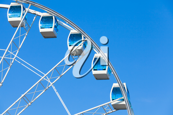 Ferris wheel with white cabins on blue sky background