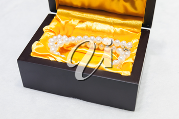 Necklace of white pearls in a gift box on a counter