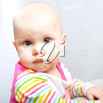 Little brown eyed baby pursed her lips. Сloseup studio portrait
