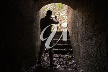 Young man is taking photo on his smartphone from dark stone tunnel