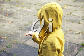 Little child in yellow raincoat playing with raindrops. Vintage stylized tonal correction photo filter effect