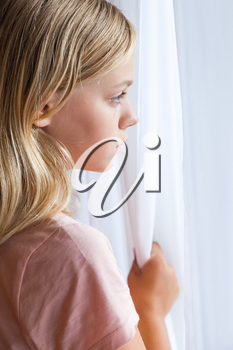 Close up vertical portrait of beautiful blond Caucasian girl standing near a window with white curtains