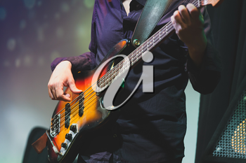Rock and roll music, bass guitar player on a stage near speakers, selective focus