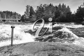 Langinkoski, fast running river water in Kotka, Finland. Black and white natural photo