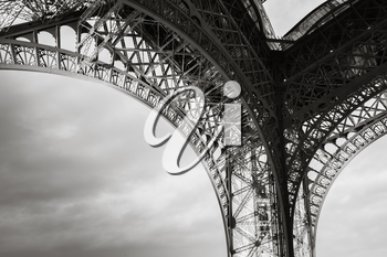 Arch of  the Eiffel tower bearings, the most popular landmark of Paris, France. Monochrome photo with retro style effect