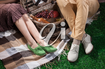 Woman's and man's legs, picnic wicker basket and checkered plaid on a green grass