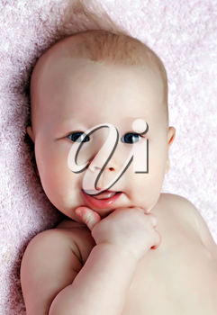 Smiling newborn baby on the pink blanket