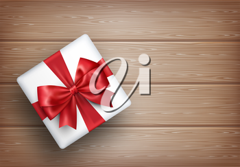 Present Gift Box with Bow on Wooden Background
