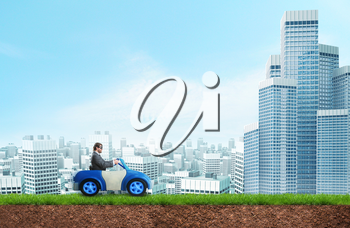 Young businessman driving a toy car towards the city