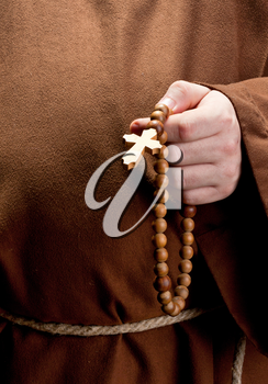 Close-up of monk hand holding wooden rosary