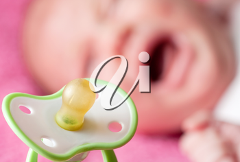 Close-up of pacifier with crying baby on background
