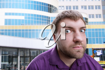 Strange bearded adult man looks at you over building background
