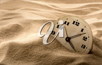 Old face of clock in sand