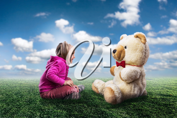 Small cute girl sits and looks at toy bear on nature background
