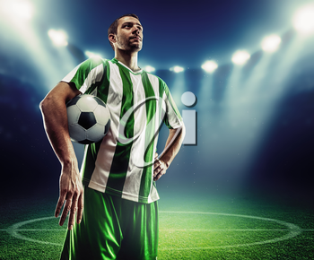 Football player holding a ball on the football ground at night