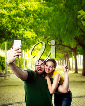 Happy man and woman making selfie in the summer park
