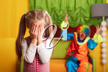 Little girl playing hide and seek with a cheerful clown in colorful costume.