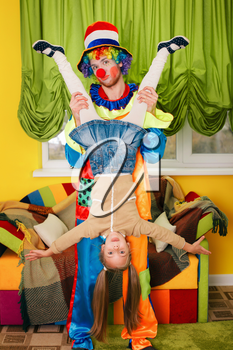 Amusing clown holds the little girl head over heels. Colourful couch on the background.