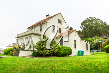 Gently slanted lawn in front of white cozy house. Estate exterior architecture.