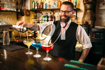Bartender with shaker making alcohol beverages behind a bar counter in nightclub
