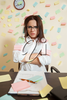 Young female bookkeeper nerves on a limit, stickers all around in office. Tired accountant manager at workplace