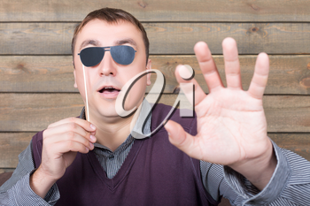 Playful man with funny sunglasses on a stick represents the blind person, wooden background. Fun photo props and accessories for shoots