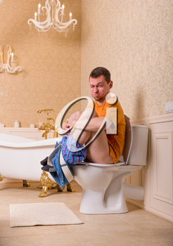 Constipation problem concept. Man with pants down sitting on the toilet bowl