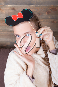 Young cute girl with funny hairstyle on a stick, wooden background. Fun photo props and accessories for shoots