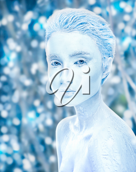 Attractive naked covered in ice woman with snowy winter forest on background. Sensuality  frosted girl. Snow frozen female, cold effect concept. Snow-covered makeup beauty