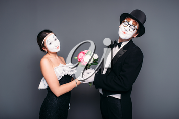 Pantomime actor and actress performing with flower bouquet. Mime theater performers posing. Comedy artists