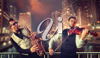 Saxophonist and violinst playing melody against night cityscape background, musical duet. Jazz-man and fiddler